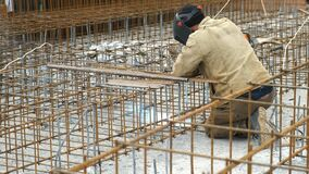 Man welder is welding metal frame for concrete foundation of the building.