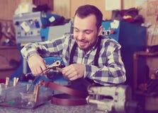 Worker working at forming hole in belt. In repair workshop Stock Image