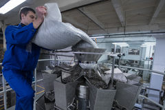 Worker working on the machine for packing loose food Stock Images