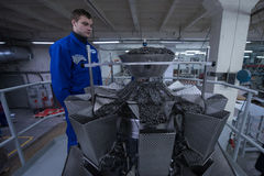 Worker working on the machine for packing loose food Royalty Free Stock Image