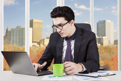 Worker working in office while enjoying coffee Royalty Free Stock Image