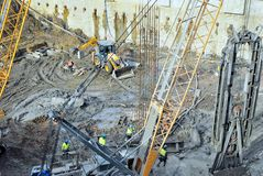 Worker working at pile driver works to set precast concrete piles in a construction high building area Stock Image