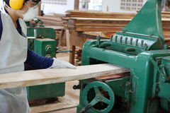 Worker is working with planing of wood machine. He is wearing safety equipment in factory Royalty Free Stock Photos