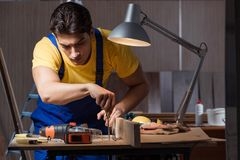 The worker working in repair workshop in woodworking concept. Worker working in repair workshop in woodworking concept Stock Image
