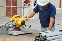 Worker Working with Saw. Construction worker sawing pieces of metal with a chop saw royalty free stock image