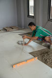 Worker working tiled at construction site. Royalty Free Stock Photography
