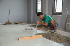 Worker working tiled at construction site. Royalty Free Stock Photo
