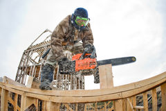 Worker. Workman with petrol-powered saw, cut up wooden brick on building site framehouse stock image