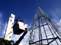 Worker works on a giant christmas tree Stock Images