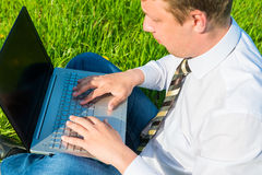 Worker works on the lawn with laptop Stock Images