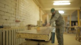 A worker works on a saw bench planing boards on a special machine, machinery. A worker works on a saw bench planing boards on a special machine, production stock footage