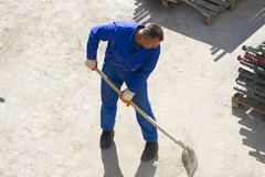 Worker works with a shovel, cleaning rubble Stock Image