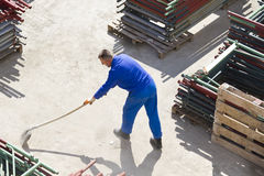 Worker works with a shovel, cleaning rubble Royalty Free Stock Image