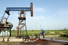 Worker with wrench on oil field. Oil worker with wrench on oil field Stock Images
