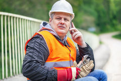 Worker with wrench and a telephone on the bridge Royalty Free Stock Photography