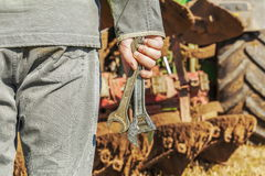 Worker with wrenches near the tractor Stock Photography