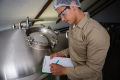 Worker writing on clipboard by storage tank. Male worker writing on clipboard by storage tank at brewery Royalty Free Stock Photography