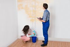 Worker Writing On Clipboard While Woman Squeezing Cloth Royalty Free Stock Image