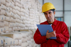 Worker Writing on Clipborad in Warehouse. Worker in distribution warehouse beside big pile of sacks Stock Image