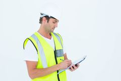 Worker writing notes on clipboard. Male worker writing notes on clipboard over white background Royalty Free Stock Photo
