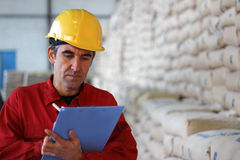 Worker writing results in Warehouse Stock Images
