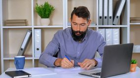 Young businessman sitting in modern office. Worker writing something on white paper then throws aside the cameras. handsome journalist or writer is in a state of stock footage
