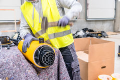 Worker with yellow vest hammering. Worker with motion blurred hammer and vest Stock Photo