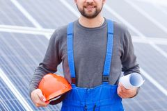 A worker holds a helmet and a paper in his hands close-up on the background of solar panels. The worker is young, with a bristle and a smile. In a blue uniform Royalty Free Stock Photography