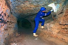 Workerman with helmet and protective suit using glowes and strong head lamp. Man check something in abandoned mine. Underground job royalty free stock images