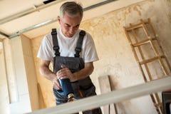 Workerr repairs the door in a carpenter`s workshop Stock Photography