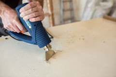 Workerr repairs the door in a carpenter`s workshop Royalty Free Stock Photography