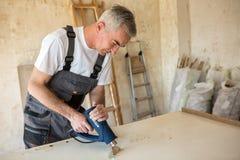 Workerr repairs the door in a carpenter`s workshop Stock Images