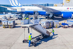 Workers with air bridge and United air aircraft Stock Photography