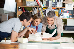 Workers Analyzing Papers Together In Factory Royalty Free Stock Image
