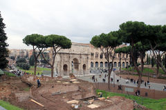 Workers in the ancient Roman forum. ROME-DECEMBER 7: workers in the ancient Roman forum area operate on a new excavation, the arch of Costantine and Coliseum in Royalty Free Stock Photography