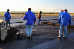 Workers applying reinforcement mesh on a surface in preparation for paving Stock Photos