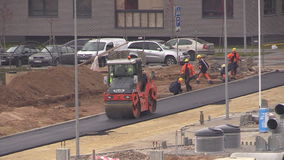 Workers and asphalt paver roller press road near flat house stock video footage