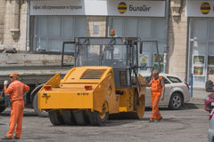 Workers and asphalt roller, road repair Royalty Free Stock Photography