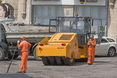 Workers and asphalt roller, road repair Stock Photos
