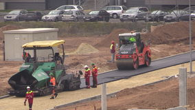 Workers on asphalt spread and roll machines in flat district. VILNIUS, LITHUANIA - NOVEMBER 17, 2014: People work on asphalt spread and roll pavement machines in stock video footage