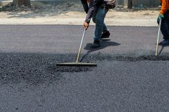 Workers on Asphalting paver machine during Road repairing works stock photos