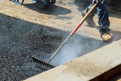 Workers on Asphalting paver during Road street repairing works. Street resurfacing. Fresh asphalt construction. Bad road Royalty Free Stock Photography
