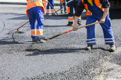 Workers on Asphalting road Royalty Free Stock Image