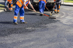 Workers on Asphalting road. Workers on Asphalting paver machine during Road street repairing works Royalty Free Stock Photo