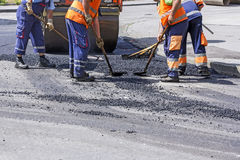 Workers on Asphalting Road. Workers on Asphalting paver machine during Road street repairing works Stock Image