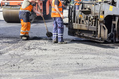 Workers on Asphalting Road. Workers on Asphalting paver machine during Road street repairing works Stock Photos