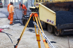 Workers asphalting the street. Survey equipment at asphalting works. Road construction and repairing works Stock Image