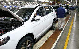 Workers assemble a car on assembly line in car factory Royalty Free Stock Images