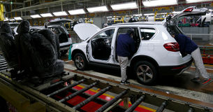 Workers assemble a car on assembly line in car factory stock photography