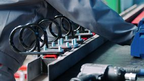 Workers assemble industrial unit from metallic parts at factory
